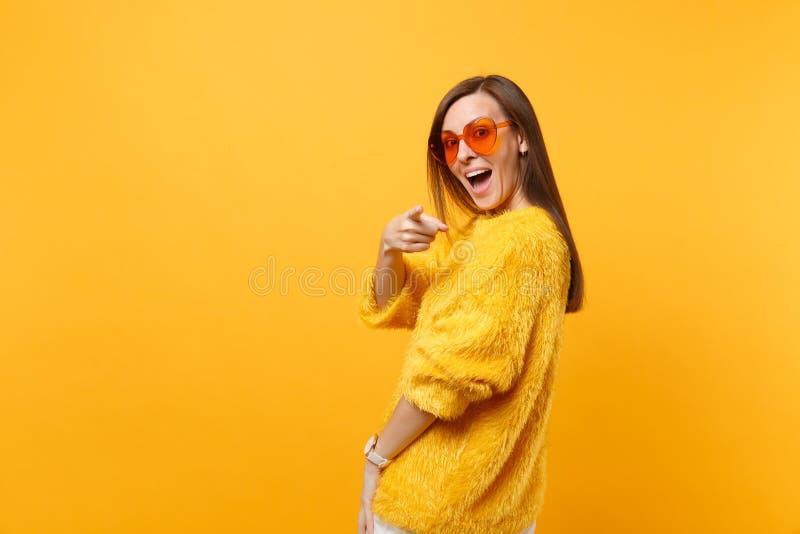 看毛皮毛线衣橙色心脏的玻璃的激动的年轻女人指向在明亮隔绝的照相机的食指 免版税库存照片