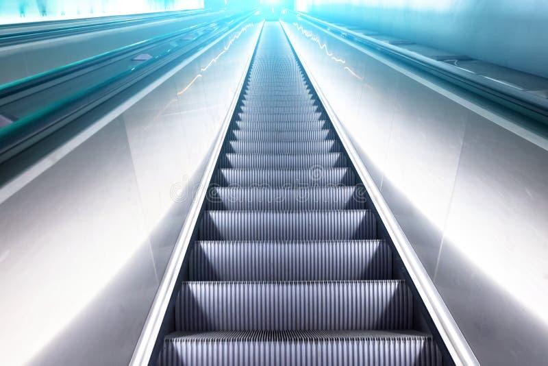 看法自动扶梯台阶在蓝色白色亮光光的上面上升 库存照片