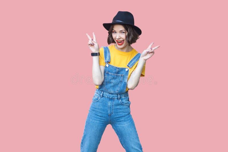 看激动的美丽的年轻女人有构成的和的黑帽会议画象黄色T恤杉和蓝色牛仔布总体的站立和 图库摄影