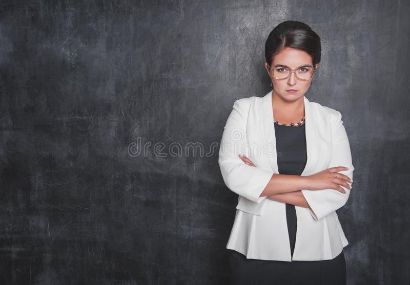 看您黑板的严肃的老师 库存照片