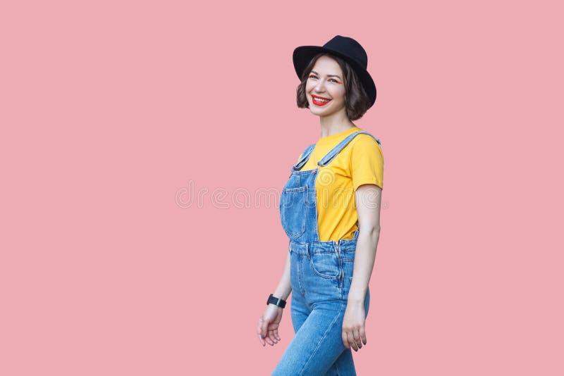 看愉快的美丽的年轻女人有构成的和的黑帽会议画象黄色T恤杉和蓝色牛仔布总体的站立和 免版税库存图片