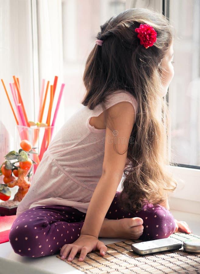 看窗口的窗台的女孩 库存图片