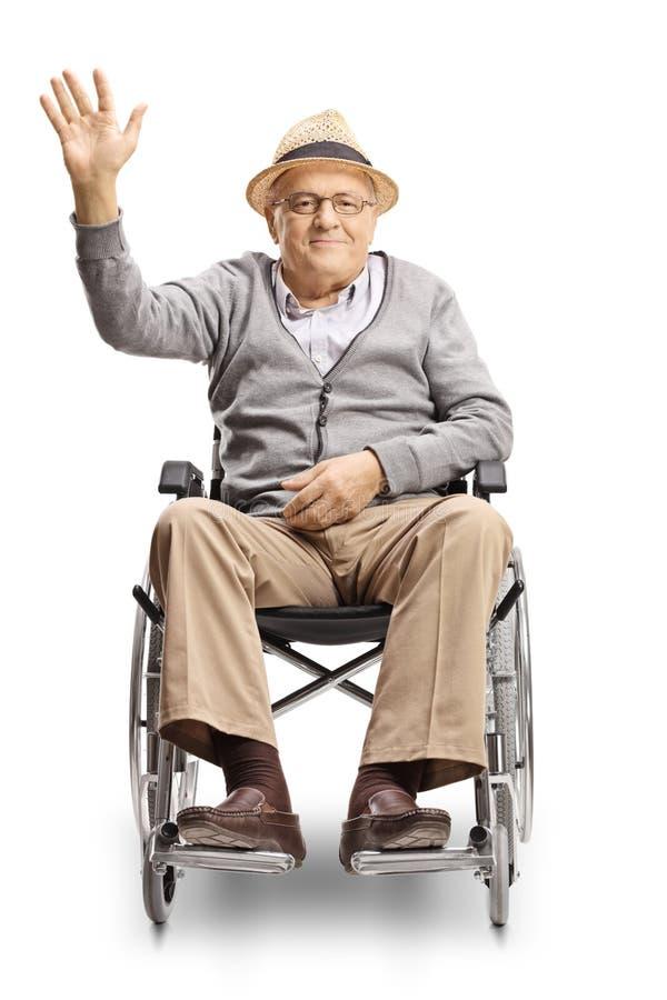 看照相机和挥动的轮椅的残疾老人 免版税库存照片
