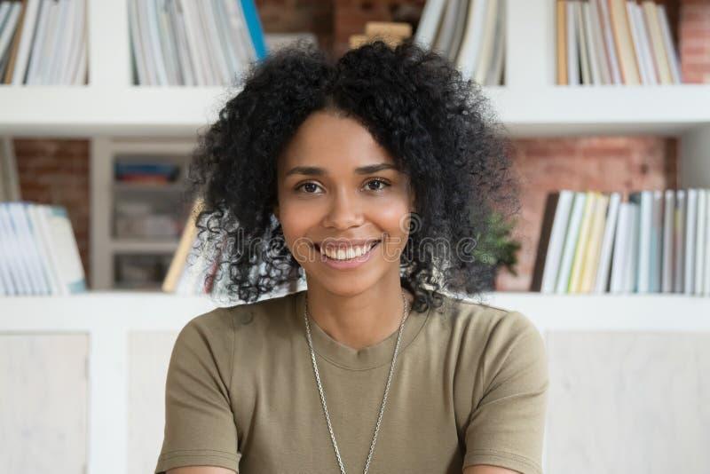 看照相机网络摄影的微笑的年轻非裔美国人的妇女 图库摄影