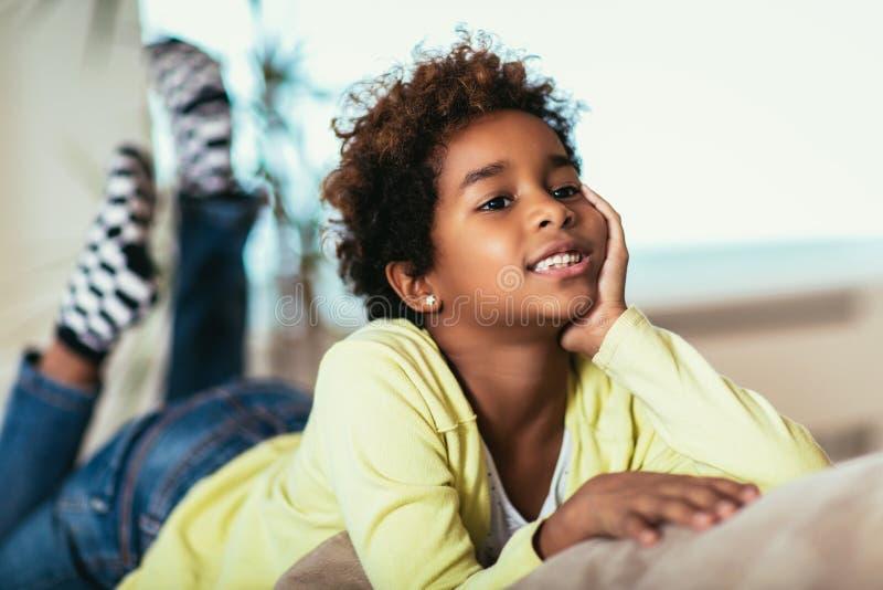 看照相机,微笑的混合的族种孩子的滑稽的矮小的非裔美国人的女孩在家摆在为画象 免版税图库摄影