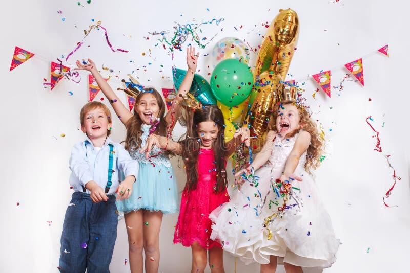看起来小组美丽的孩子投掷五颜六色的五彩纸屑和愉快在生日宴会 库存照片