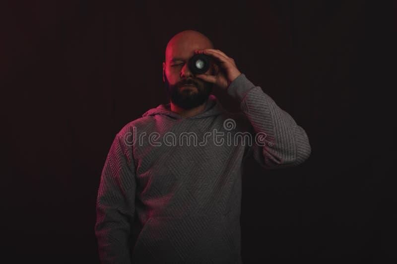 看通过照片透镜的摄影师在有葡萄酒或减速火箭的照明设备的演播室 免版税图库摄影