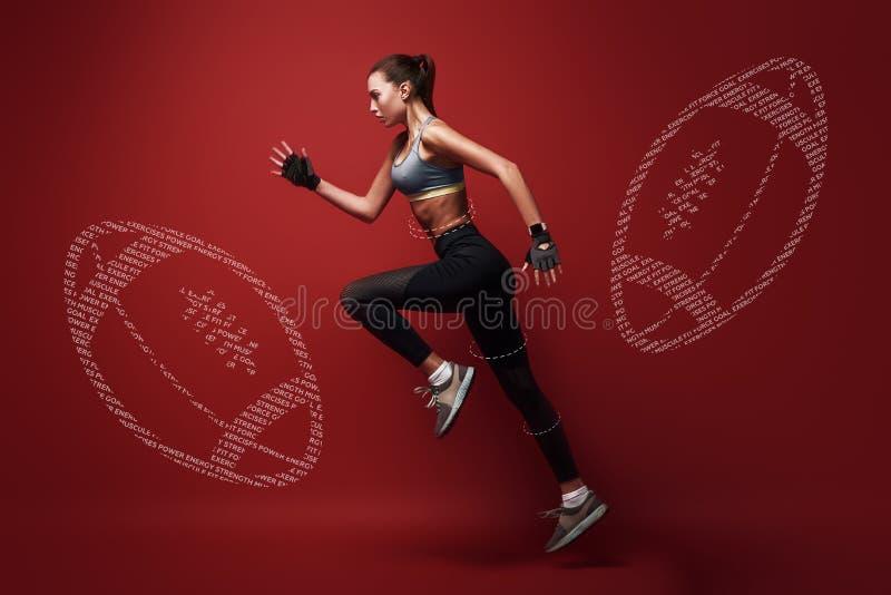 看适合,适合 在位置的年轻,有吸引力的女运动员身分的奔跑,被隔绝在红色背景 库存照片