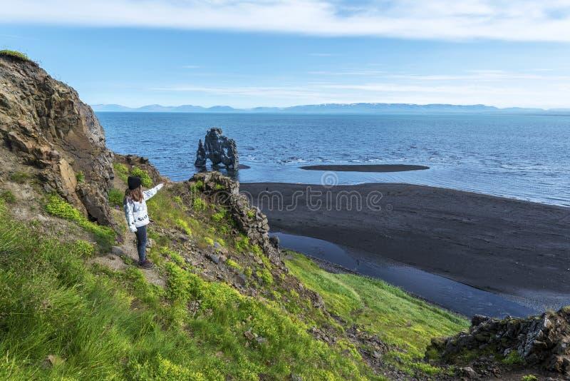 看Hvitserkur玄武岩堆的女孩游人洗涤用Hindisvik海湾水在冰岛西北部 免版税库存图片