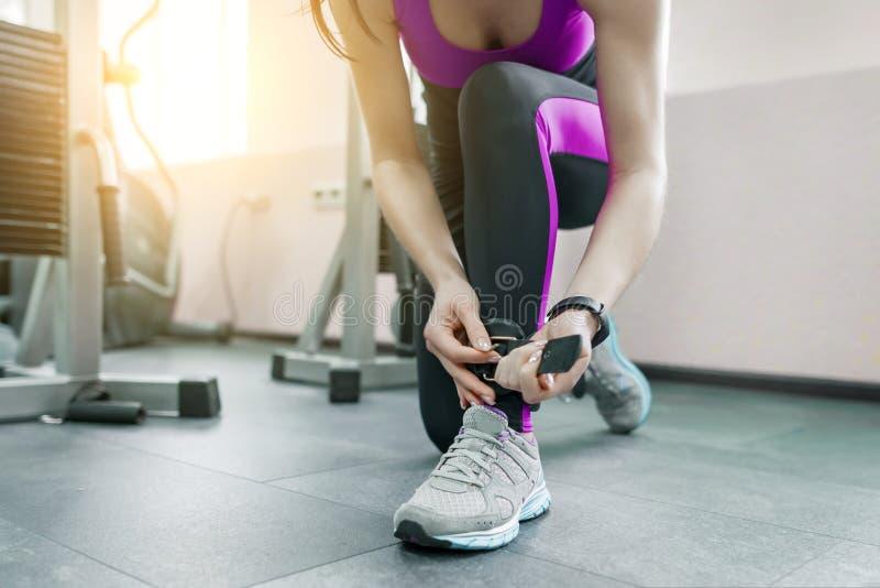 皮带的年轻女人佩带皮革脚腕在健身房的健身机器准备行使 健身,体育,训练,人们 库存照片