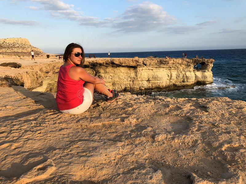 的浅色皮肤的女孩太阳镜和桃红色T恤杉在岸 免版税图库摄影