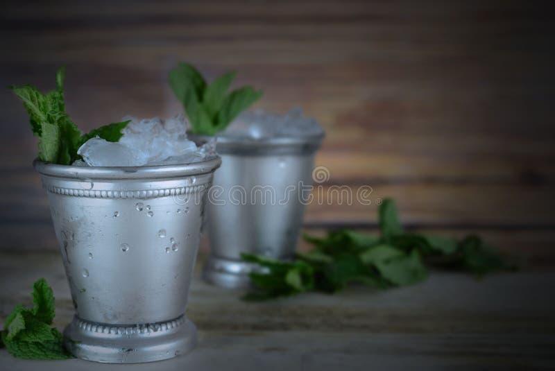的肯塔基德比图象在显示有被击碎的冰和新鲜薄荷的5月两个银色薄荷朱利酒杯子在一个土气设置 免版税库存照片
