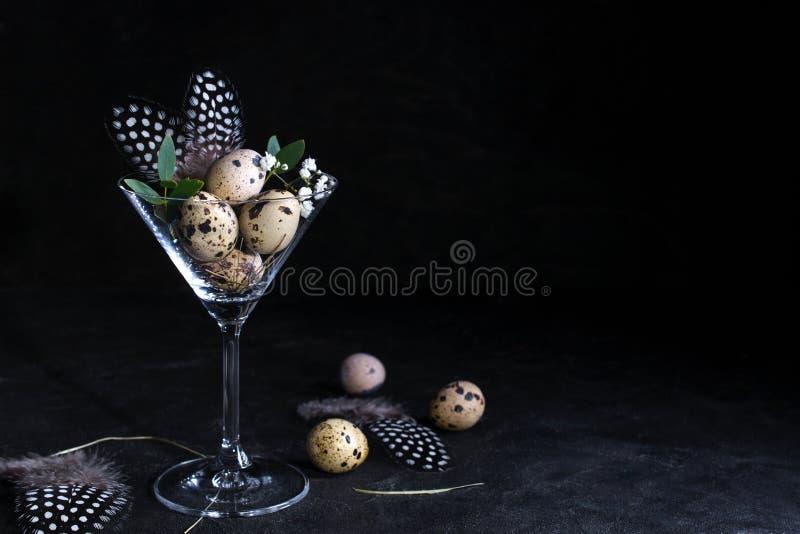 现代复活节室内装饰想法  在鸡尾酒杯的鹌鹑蛋在黑暗的生锈的背景 Copyspace 库存照片
