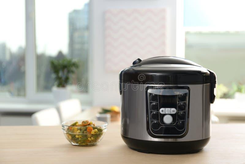 现代多烹饪器材和成份在桌上在厨房里 免版税库存照片