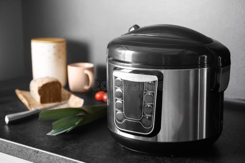 现代多烹饪器材和成份在桌上在厨房里 免版税库存图片