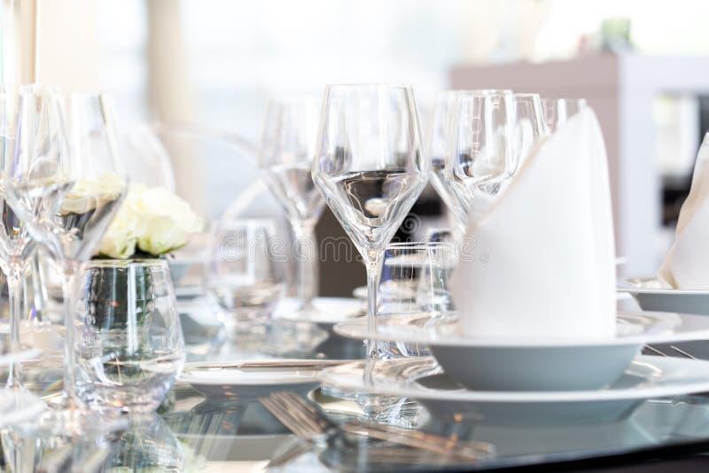 现代宴会设置细节在玻璃桌上的 模糊的背景 库存图片