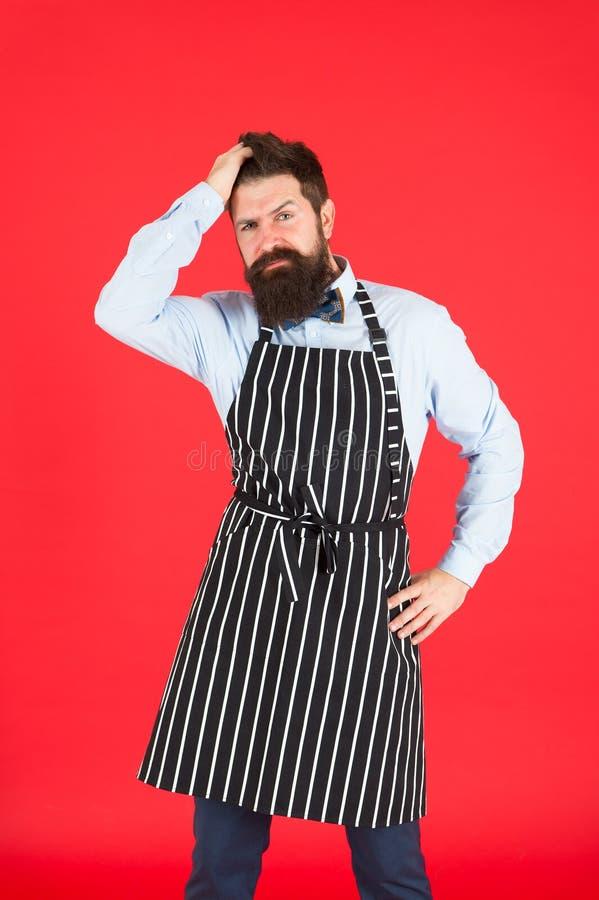 现代咖啡馆概念 烹调现代饭食 有胡子厨师行家围裙的人 行家厨师厨师红色背景 博若莱红葡萄酒 免版税库存图片