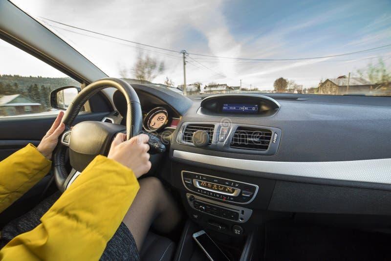 现代汽车内部用在方向盘的司机女性手,外面冬天多雪的风景 安全驾驶的概念 免版税库存照片