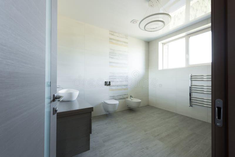 现代灰色卫生间内部有洗手间和净身盆视图 免版税库存图片