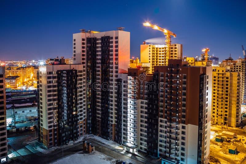 现代高多层的居民住房的建筑,夜鸟瞰图建筑场地 免版税库存照片