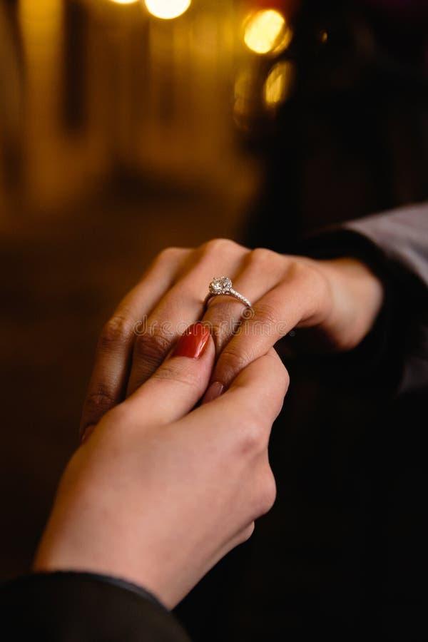 现实提案:新娘的朋友检查定婚戒指-与一颗大宝石的一个圆环 免版税库存照片