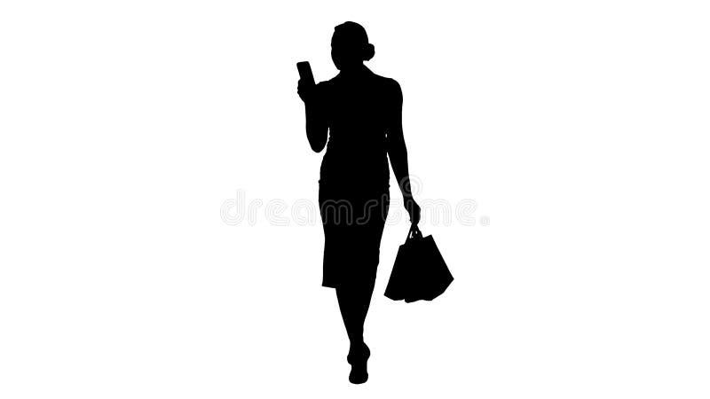 现出轮廓看在智能手机和拿着购物带来的美丽的可爱的妇女,当走时 库存照片