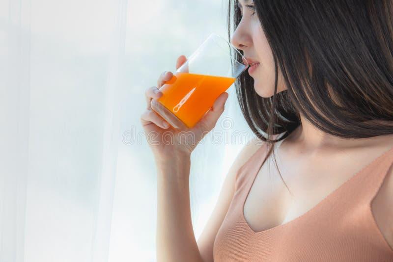 玻璃妇女健康饮用的新鲜的橙汁过去  免版税图库摄影