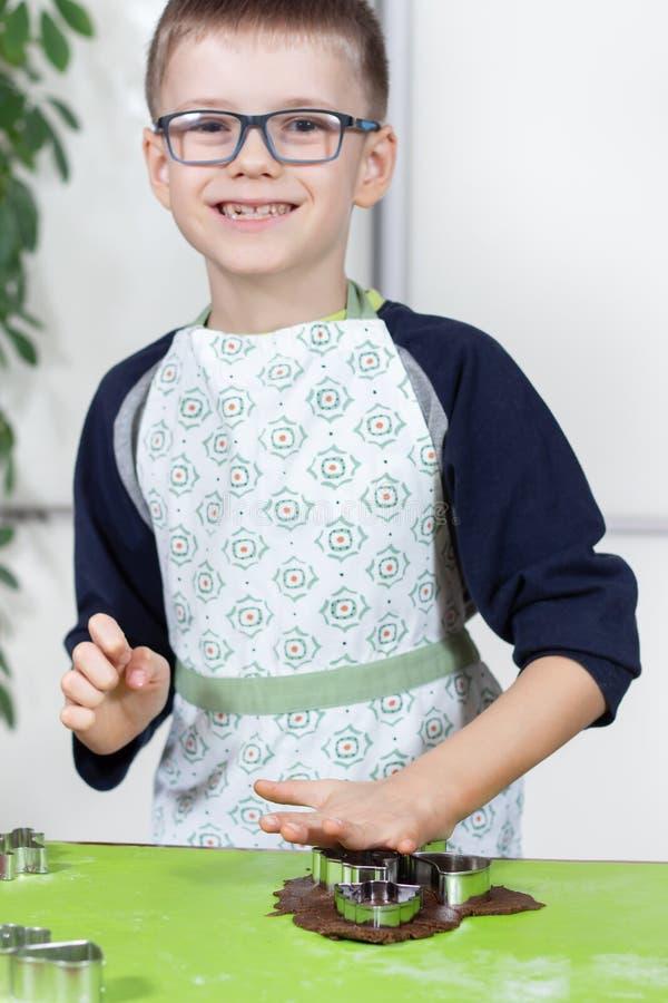 玻璃和厨房围裙的微笑的接合的男孩从金属型紧压形状在一个棕色面团 免版税库存照片