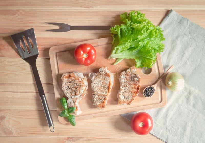烤猪肉牛排、沙拉叶子和新鲜的蕃茄 免版税图库摄影