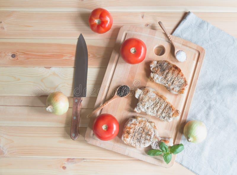 烤猪肉牛排、新鲜蔬菜和调味料在切板 免版税图库摄影