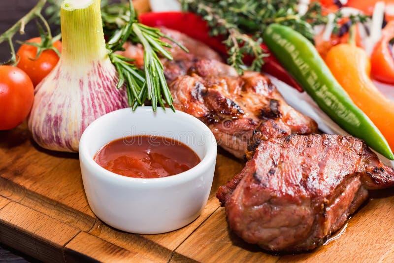 烤肉脖子的关闭用香料、菜和番茄酱在木板 库存照片