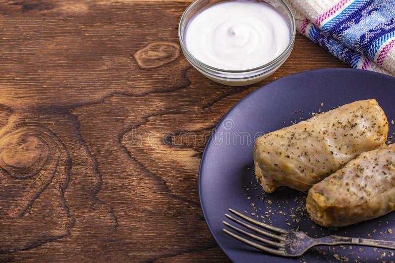 热的圆白菜卷用米,与酸性稀奶油的肉在黏土盘 Kelem dolmasi -白菜卷叶子 圆白菜dolma,普遍所有 免版税图库摄影
