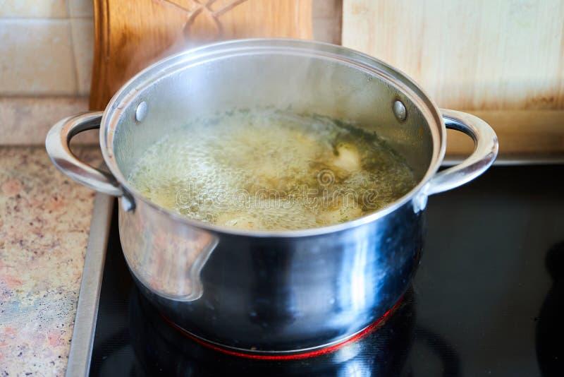 烹调在平底深锅的汤在一块玻璃陶瓷板材 免版税图库摄影