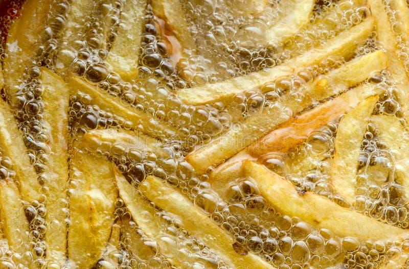 烹调在油特写镜头的薯条,背景 油煎与泡影的土豆 库存照片