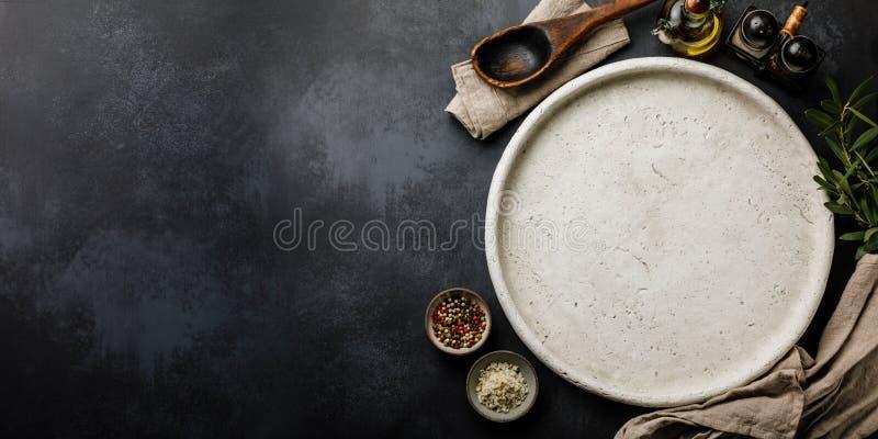 烹调的比萨和香料圆的石盘在黑暗的具体背景表面拷贝空间 库存照片