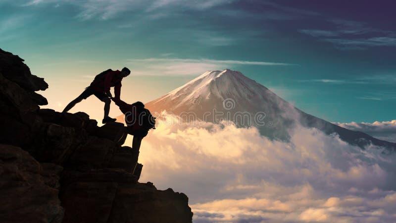 爬上在山峰顶的年轻亚裔夫妇徒步旅行者在山富士附近 上升,帮助和团队工作概念 库存照片