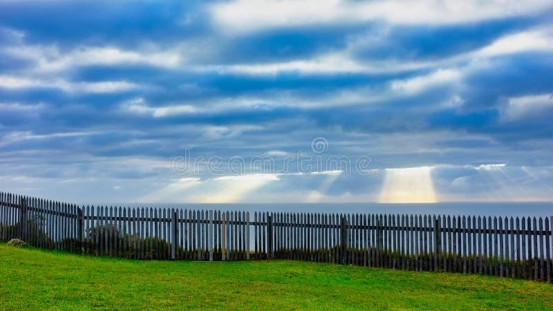 爬行通过在海洋的密集的早晨云彩的太阳光芒 库存照片
