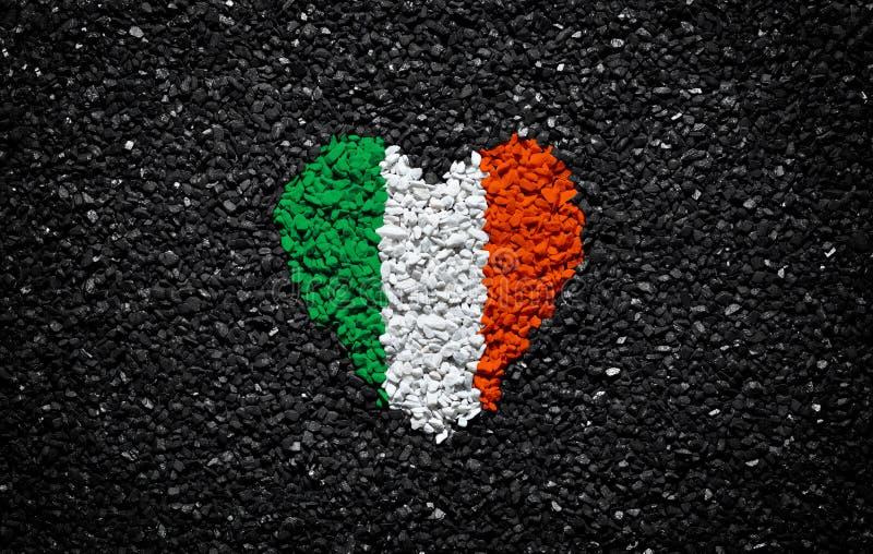 爱尔兰的旗子,爱尔兰旗子、心脏在黑背景,石头、石渣和木瓦,织地不很细墙纸,情人节 免版税库存图片