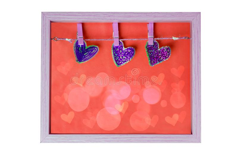 爱的声明与三装饰心脏的在在a与红色背景纹理隔绝的一个木制框架的一chlothesline 免版税图库摄影