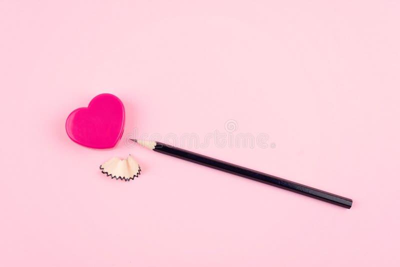 爱,关系,言情概念 桃红色心脏铅笔刀和铅笔有削片的在桃红色背景 库存图片