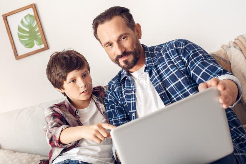 父亲和一点儿子在家坐在看屏幕的膝上型计算机的沙发电影震惊 免版税库存照片