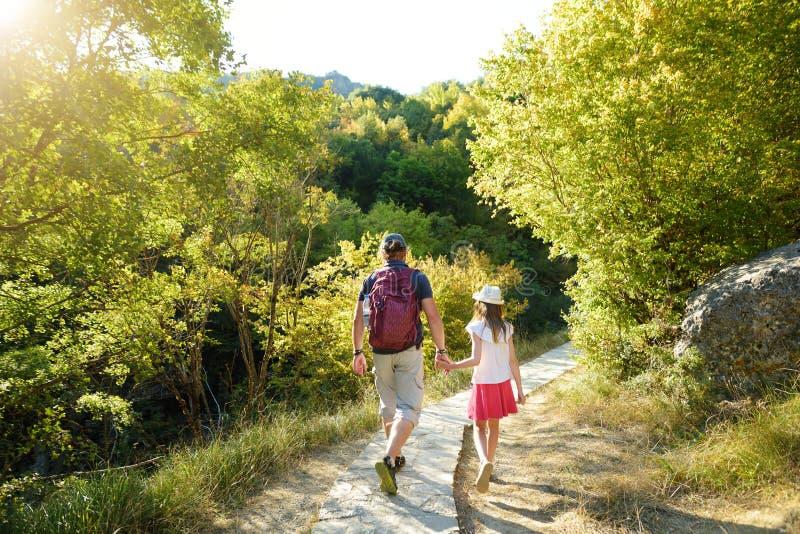 父亲和女儿获得远足在温暖和晴朗的夏日的乐趣在家庭度假期间在扎戈里亚,希腊 免版税库存图片