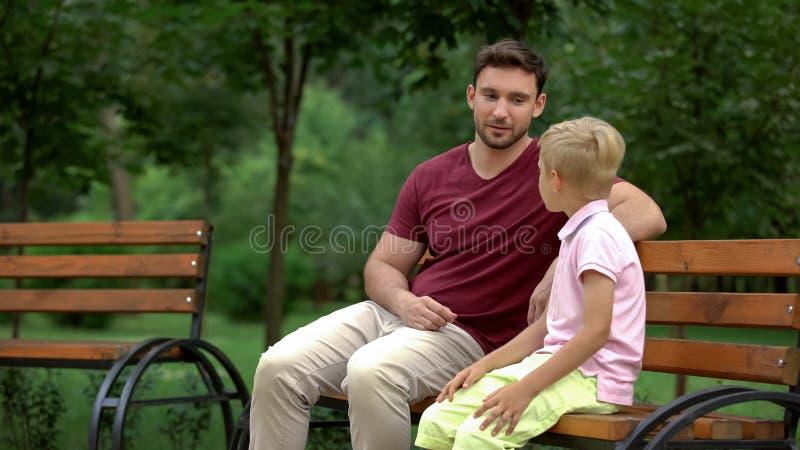 父亲和儿子坐长凳在公园,人谈话,一起花费时间 图库摄影