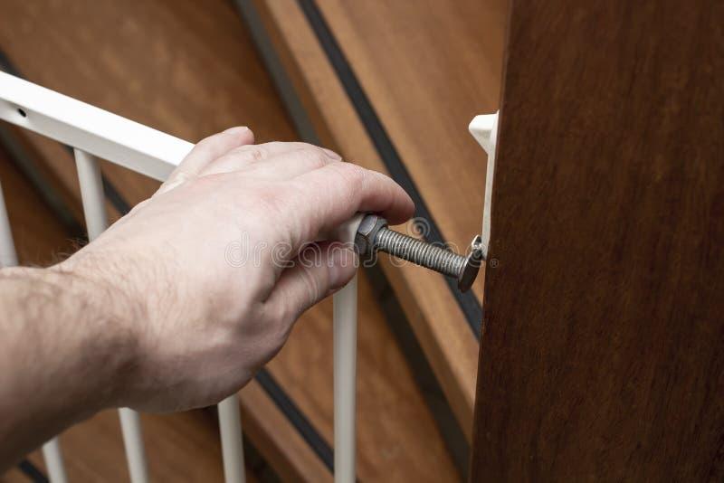 父亲的手小心地关闭安全门在木台阶的底部 儿童安全概念 免版税图库摄影