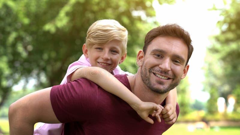 爸爸和儿子肩扛在周末在公园,愉快的童年乘坐,休息的家庭 免版税库存照片