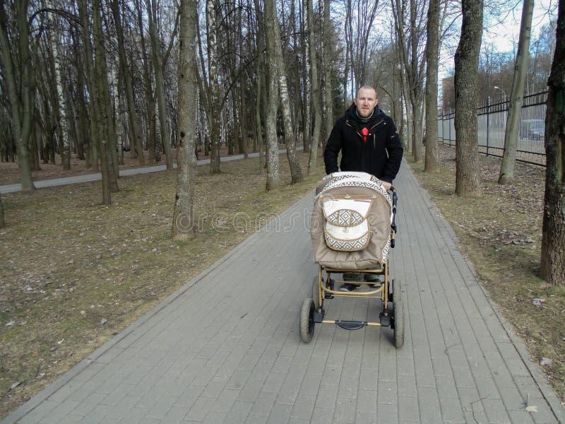 爸爸滚动有一新出生的婴儿推车沿森林公园的道路 免版税库存照片