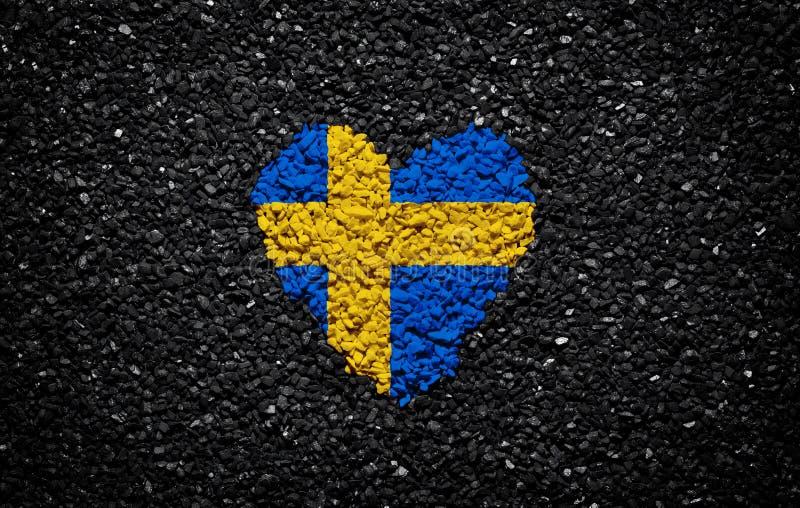 瑞典的旗子,瑞典旗子、心脏在黑背景,石头、石渣和木瓦,织地不很细墙纸 库存图片