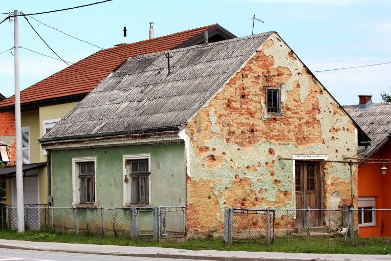 炮弹碎片损坏了小家庭房子在所有者现在放弃的战争期间被围拢与未割减的草和打破部分地生锈 库存图片
