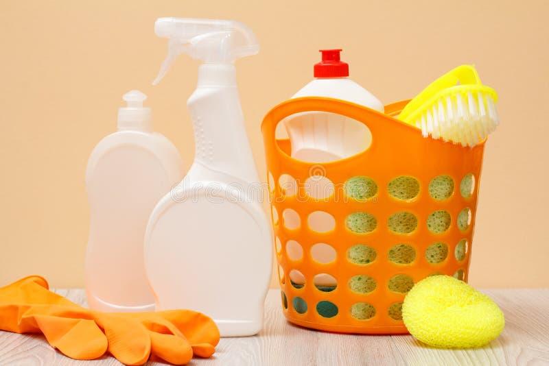瓶洗碗盘行为液体、橡胶手套、篮子和海绵在米黄背景 免版税库存照片