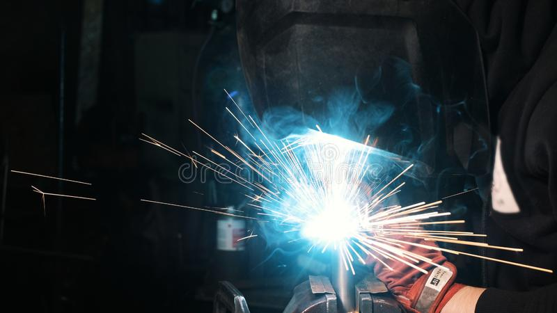 焊接工厂的男性工作者焊接面具的 焊接在一套工厂设备 免版税库存照片